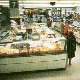 Delicatessen island counter offering lots of different cheeses featured in the major Woolworth city centre stores in the Seventies