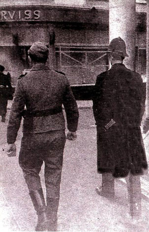 An infamous picture from World War II Jersey, as a uniformed British policeman and a German soldier walk side by side in St Helier, Jersey, Channel Islands CI.