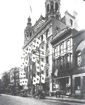 Rival dimestores in North Queen Street, Lancaster PA in 1910 - McCrory's in the foreground in front of Frank Woolworth's first skyscraper, bedecked with flags