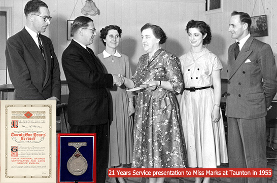 21 years service presentation to Miss Marks at Woolworth's Taunton in 1955. The award was made by the Store Manager, Mr. J.K.R. Mandley (shaking hands with Miss Marks), Mr Rouse looks on to their left, with Deputy Manager Bill Pell on the far right